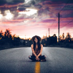 warren-wong-275574-girl-sitting-in-the-middle-of-distant-paved-road-unsplash image