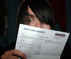 man peeking over the top of a credit card statement